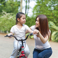 Asian mother teaching little girl to ride a bike